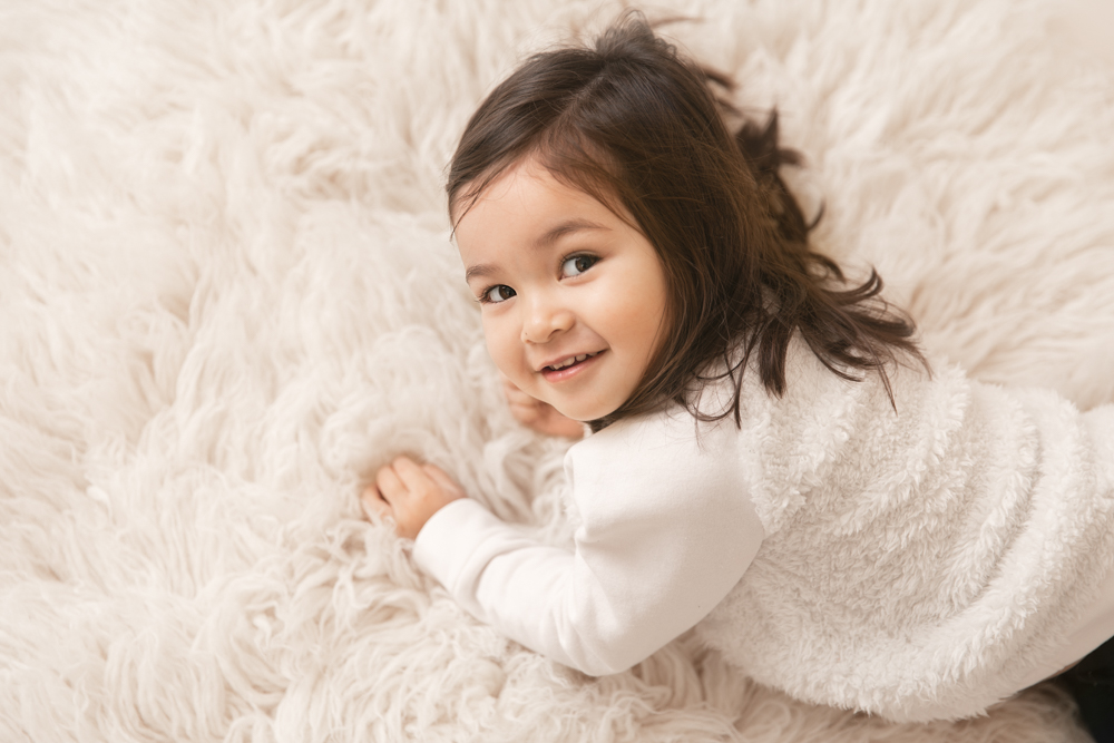 Toddler girl laying on cream rug